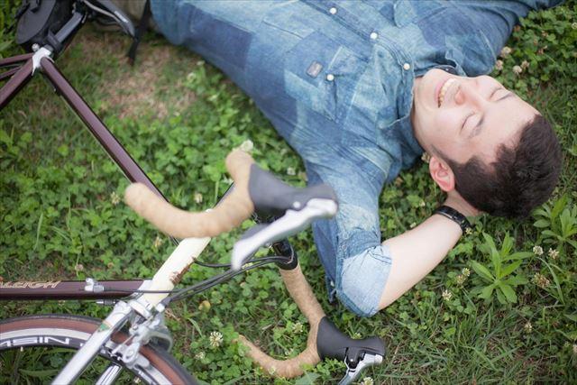 草原に寝転がる自転車乗り